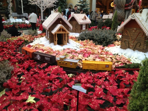 Hundreds of poinsettias form the landscape for artful gingerbread houses