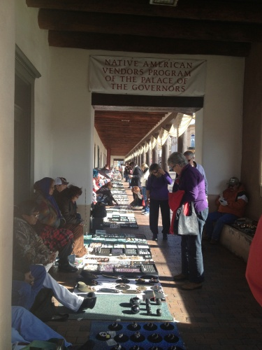 Native American artisans line the sidewalk under the portal of the Palace of the Governors.