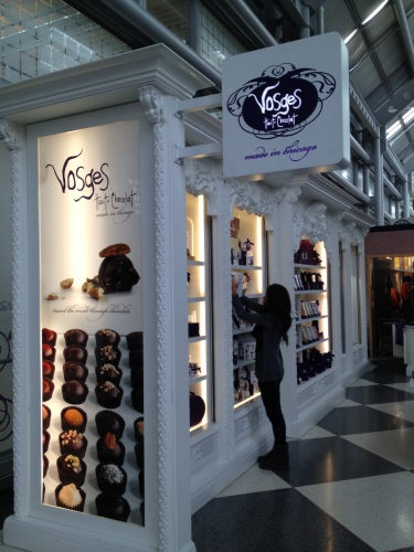 A clerk straightens the artisan chocolates at Vosges