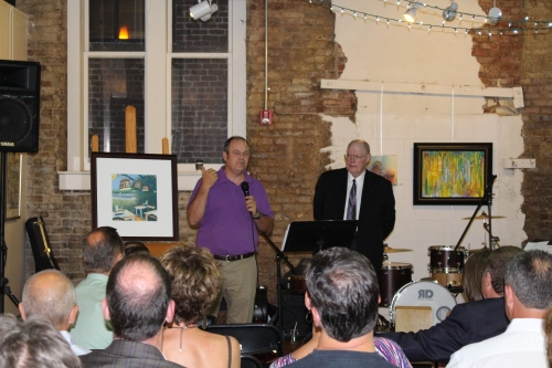 Artist Mike Berry gives background information on his painting while auctioneer, Harold Reed, looks on.
