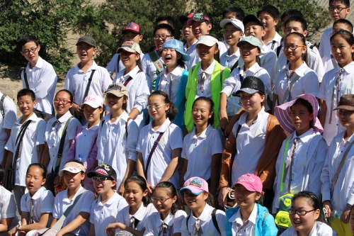 A tour group pauses before hiking The Great Wall for a picture to capture the moment.