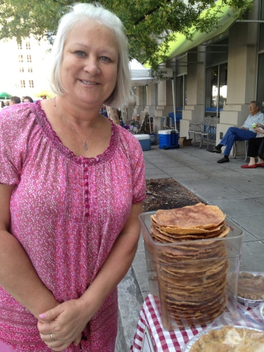"Cathy Dunn stands next to a tall stack of shoe soles from Frances Chauvin, the ""Pie Lady."""