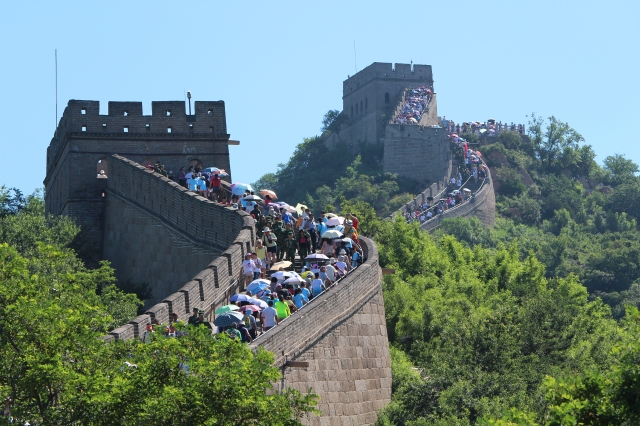 A glimpse of the many people (with umbrellas on this hot day) at the Great Wall at Badaling.