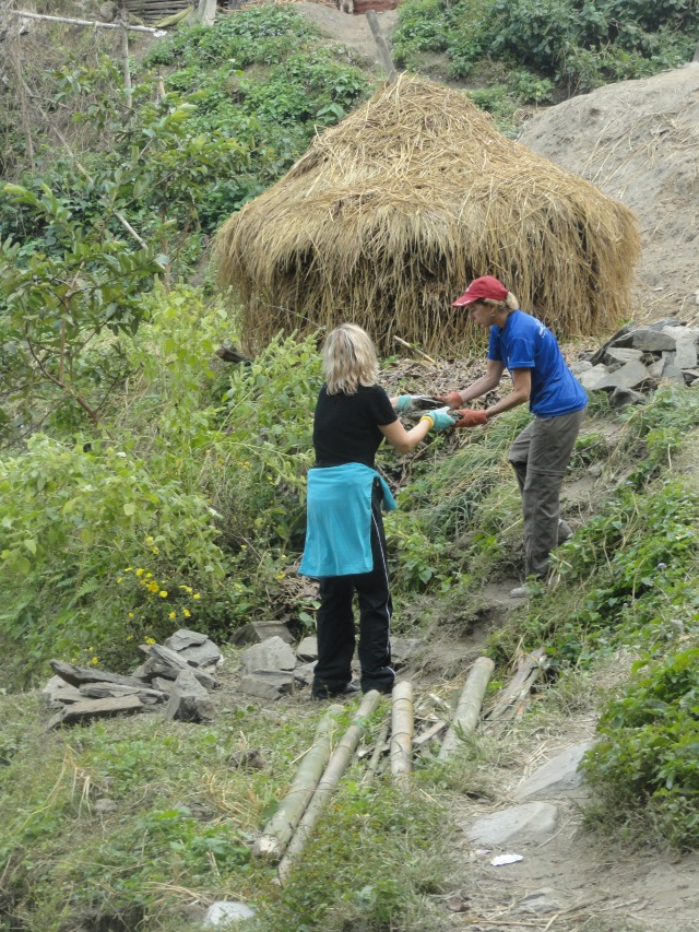 Morena Constantinou and Susan West of Knoxville pass rocks up the mountainside in Nepal.