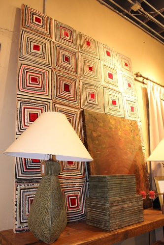 A quilt mounted on a stretcher frame fills a wall with color