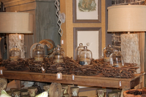 Twig nests lined up on a sofa table hold glass domes and scented candles.