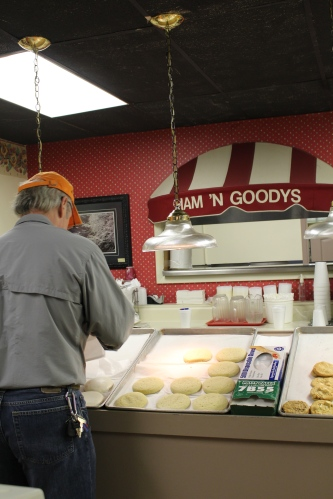 Steve Shoemaker reaches into the rows of tea cakes to fill an eager customer's order.