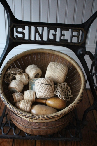 Collection of crochet thread and sock darners fill a basket in the Lilac Room