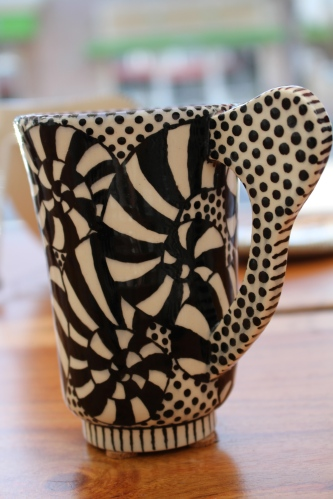 Adorned with a bold graphic, this mug catches your attention in the window of Florida Craftsmen.