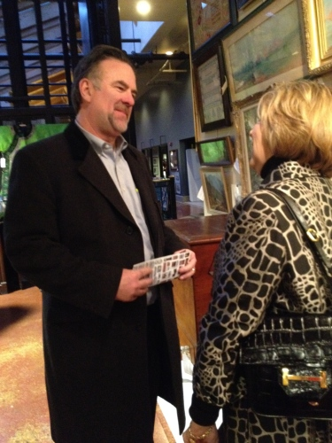 Jimmy Buckner, owner of Latitude 35, learns more about the Wiley painting from Marilyn Henry