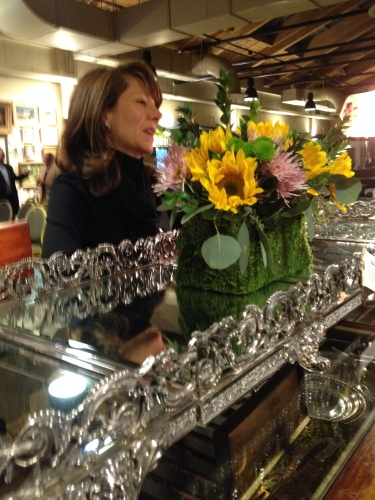 Sarah Campbell Drury of Case Antiques talking with a guest at the preview event about the silver pieces up for bid