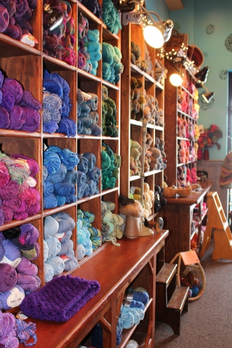Wall of yarn organized by color invites you to touch and see.