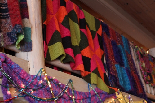 Colorful creations hang from above at Keep Me In Stitches