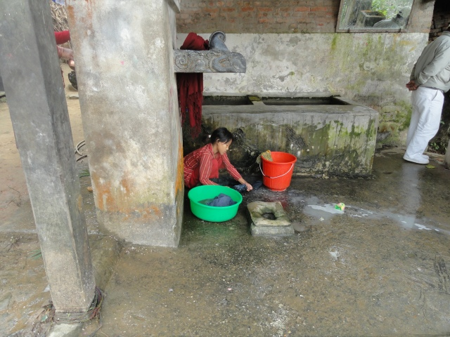 Woman in Nepal bathing in public bath area