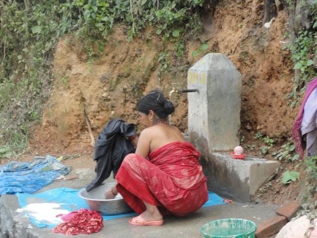 Woman in Nepal bathing alongside hiking trail
