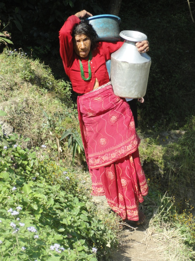 Woman carrying laundry and jug of water