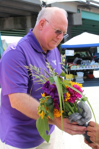 Jim Mouch buys bouquet at Decatur Farmers Market