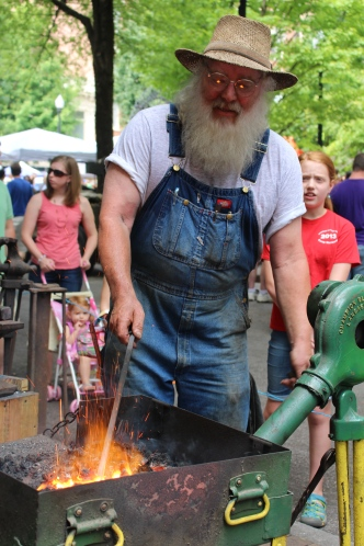 Mike Rose demonstrates blacksmithing techniques in Krutch Park