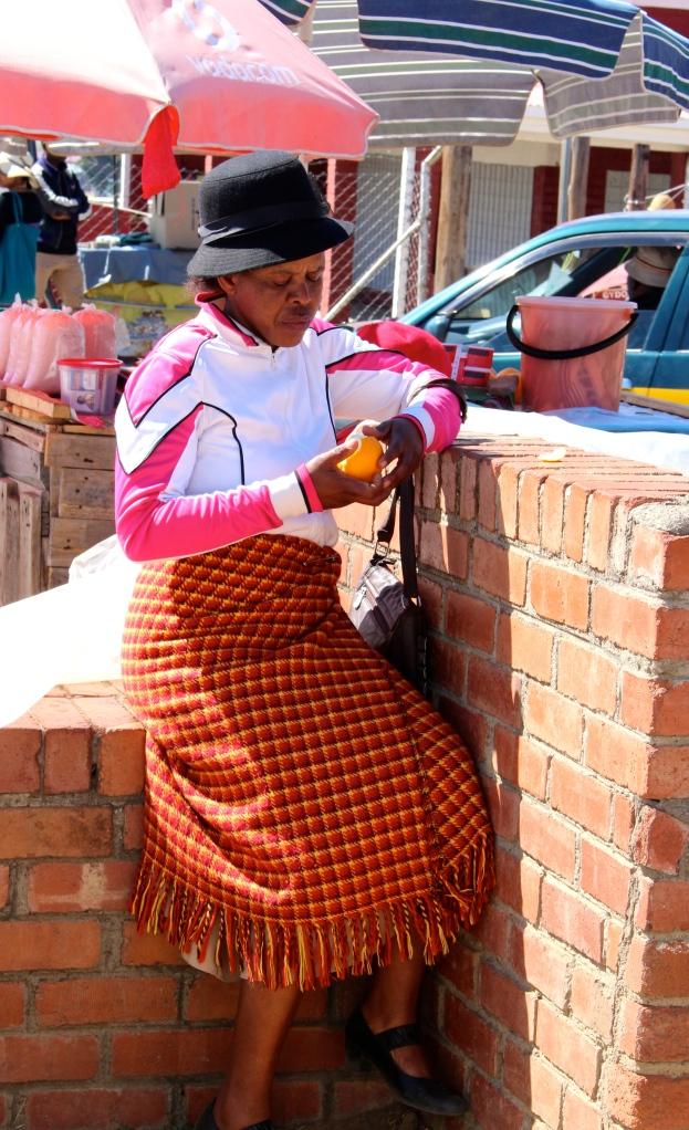 Lady eating orange in Lesotho