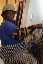 Utilizing many colors at once, this weaver works from the small picture to her left.
