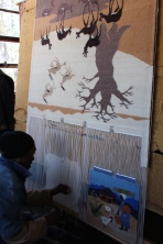 Weaver with tapestry depicting African landscape