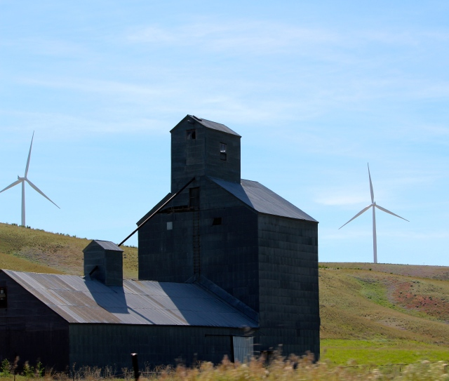 Barn silhouette against wind farm