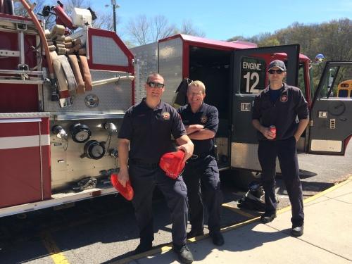 Firefighters Chris Justice, Mike Pickett, and Adam Noe passed out lots of red firemen's hats.
