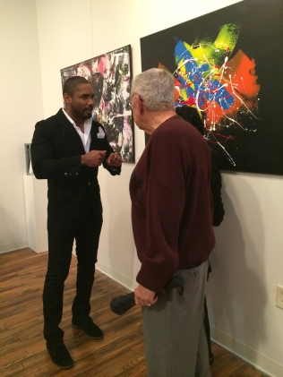Angel Blanco (left) talks with a guest at his art opening at the Emporium