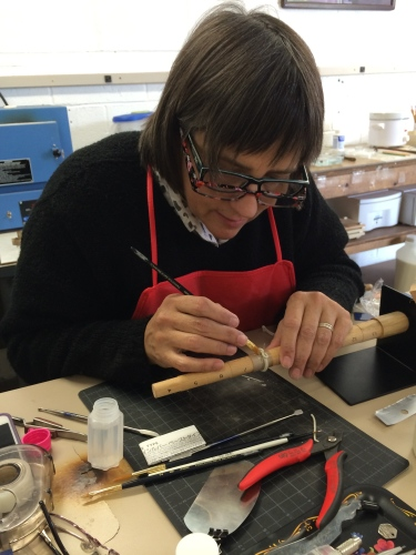 Focused on shaping a silver ring, Judi Talley shares her craft while continuously working.