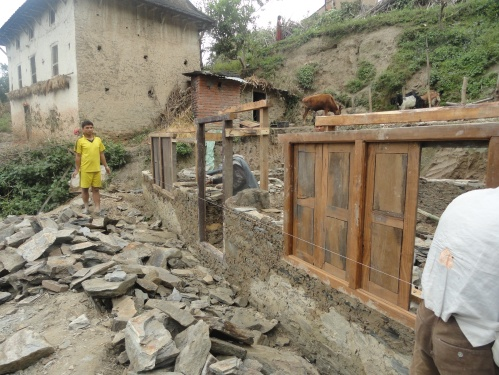 Adding doors and windows to a new home in Nepal constructed of stone and mud