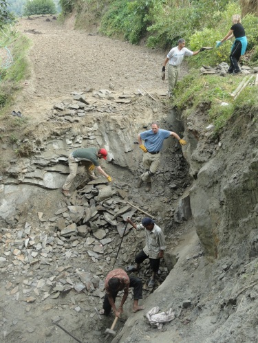 Homeowner in Nepal breaks up stone from a quarry on his mountainside property