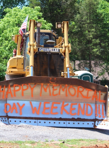 As workers paused for a long weekend, they left this sign on the machinery in the vacant lot they were clearing.  Memorial Day, 2015 -- Knoxville, Tennessee