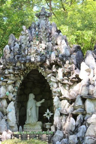Shrine incorporating seashells, cement, found objects, and miniature statures -- Ave Maria Grotto