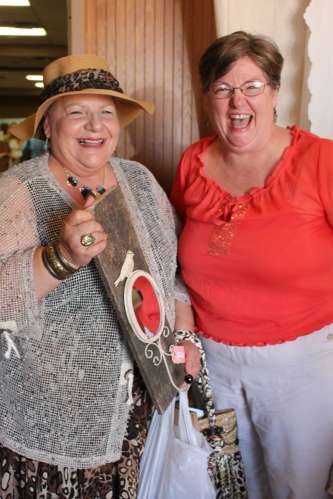 Lynn Lowery of Knoxville shows off her purchases to Carla, one of the greeters at The Traveling Bazaar.
