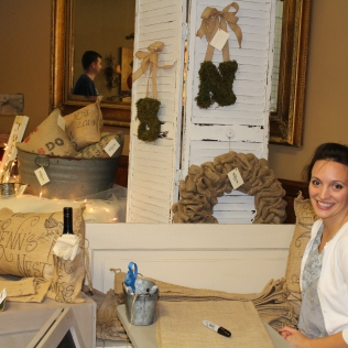 Jessica Wrenn Hill in her both surrounded by antiques and farmhouse decor.