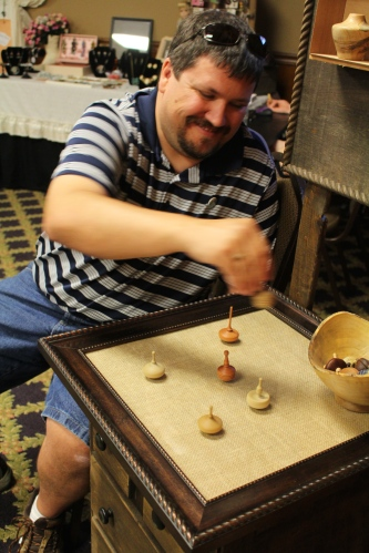 It's not all work at The Traveling Bazaar.  Randy Gleckner takes to spinning tops in his booth at The Traveling Bazaar.