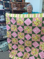 Marilyn holds quilt made with a 5-yard bundle at Loose Threads