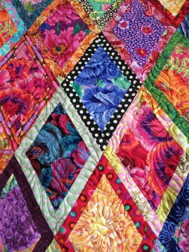 Vivid fabrics by Kaffe Fassett liven up a traditional quilt pattern.