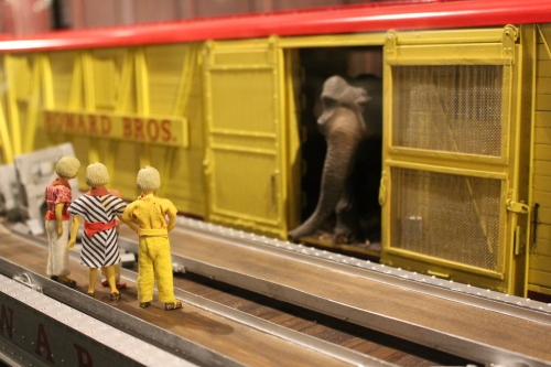 And elephant peeks out the door of a yellow train car belonging to Howard Bros. Circus.