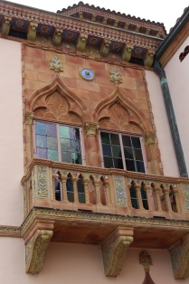 Graceful windows and balcony against patterns of terra cotta tiles.