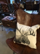 Leather chair holds a screened pillow at Elm & Iron OTR