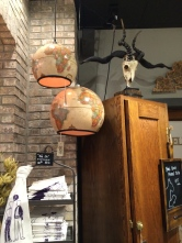 Globe lamps hang near a wooden cabinet topped with an animal skull!