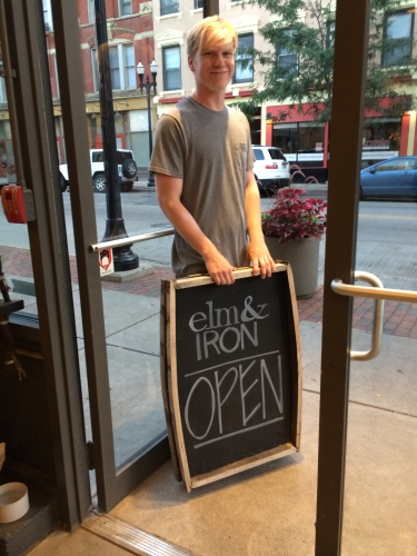 Chad gets ready to move the chalkboard at the new Elm & Iron OTR in Cincinnati.