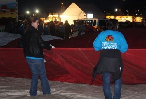 Balloon enthusiasts are up early unrolling their balloons on tarps laid out on their designated spaces on the launch field.