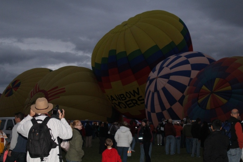 Balloons are lined up, or so it seems, and filled with warm air in the early morning darkness