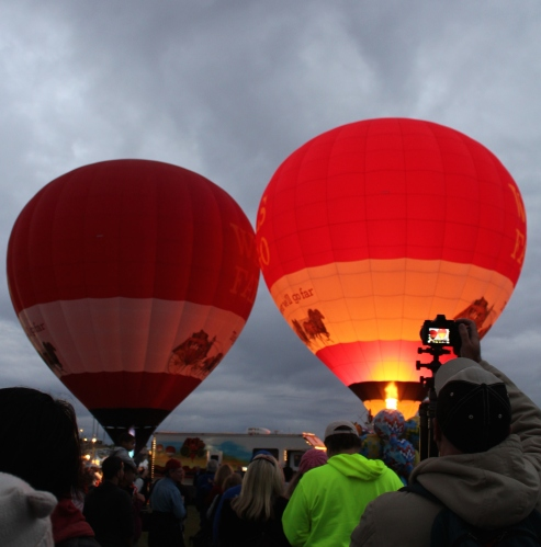The reward for rising early?  Beautiful lighted balloons against gray morning skies.