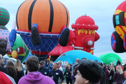 A crowded launch field as spectators move in to watch balloons lift off at the Special Shapes Rodeo.