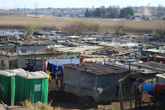 Huge area of tin roof dwellings bounded by toilets on one side and fences on another: Soweto, South Africa.