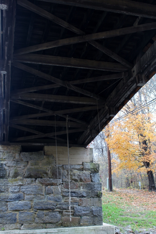 Looking under the bridge at wood beams and what seems to be rope just waiting to be grabbed!