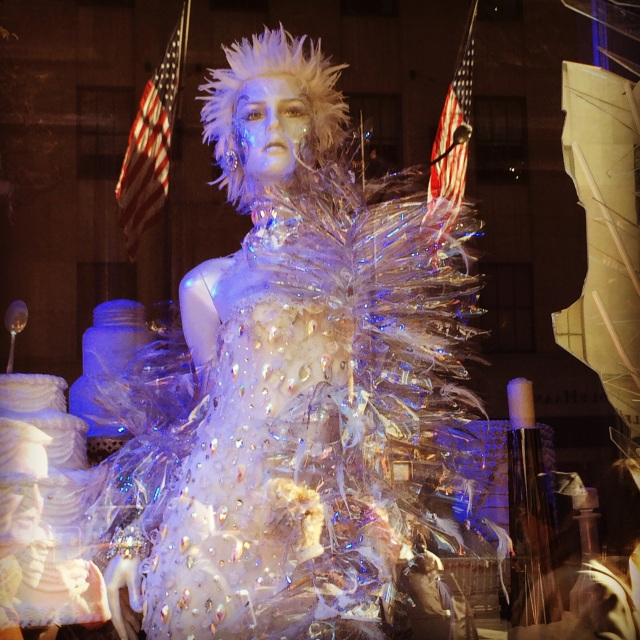 "This mannequin looks assertive and poised as she ""walks"" toward the crowd in a window at Saks Fifth Avenue. The flags are reflections from the building across the street."